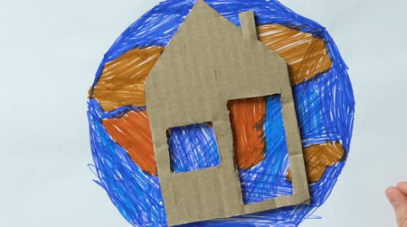 konzervace : Little child putting cardboard house and toy heart on planet picture, save Earth