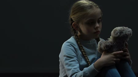 sitting room : Little girl hugging toy bear sitting in dark empty room, lack of parental care Stock Footage