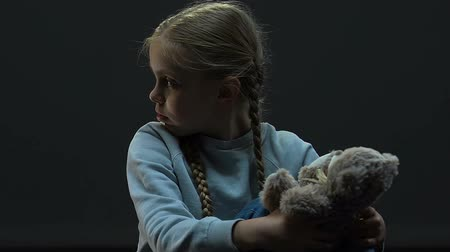 maltreatment : Small girl sitting in darkness playing with toy bear, family abuse, maltreatment
