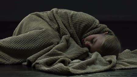 maltreatment : Scared girl flinching from fear, lying on floor and covering head with blanket