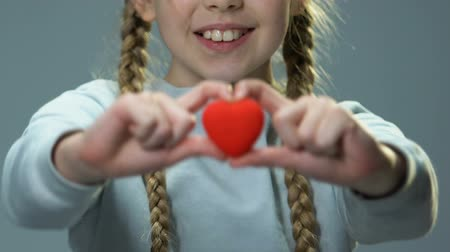 humanidade : Happy cute girl showing toy heart into camera, feeling herself loved and needed Stock Footage