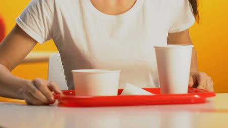insalubre : Slim female student carrying fast food tray in cafeteria, sitting at table