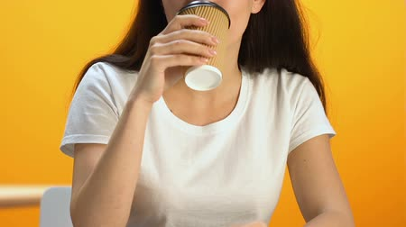 plezant : Young female enjoying taste of hot beverage, smiling into camera energetic drink