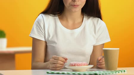 kekler : Slim woman snacking on delicious glazed doughnut and drinking hot beverage Stok Video