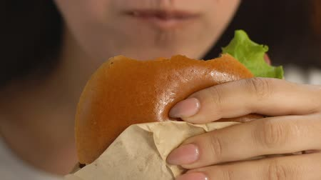 нездоровое питание : Woman enjoying greasy burger, junk food addiction, calories and saturated fat