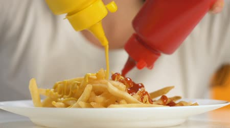 snoepen : Female hands pouring ketchup and mustard into french fries, extra calorie meal
