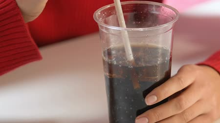 açucarado : Female hands holding plastic glass with soda, unhealthy sugary drinks, close-up