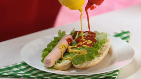 musztarda : Person cooking hot dog, pouring mustard and ketchup into fast food meal, snack