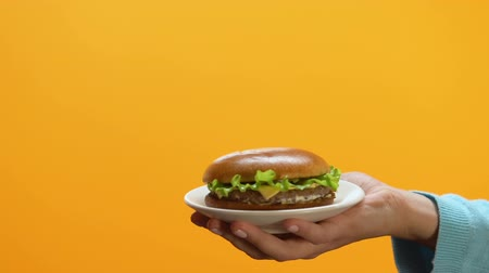 harmful habit : Female refusing high calorie burger offered by person, healthy eating habit Stock Footage