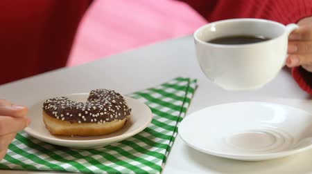 застекленный : Person eating glazed doughnut and drinking coffee at cafe, addiction to sweets