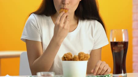 chicken pieces : Pleased female enjoying crispy fried chicken and soda in fast food restaurant Stock Footage
