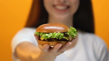 cholesterol : Young smiling lady proposing yummy hamburger, fast food restaurant, close up