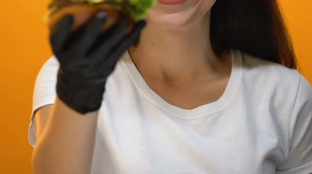 cheirando : Fast food restaurant client showing burger into camera, tasty unhealthy food
