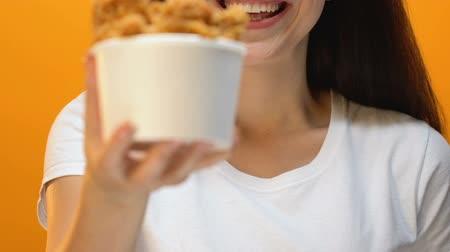 unhealthy eating : Happy girl sniffing and showing at camera crispy fried chicken in bucket closeup Stock Footage