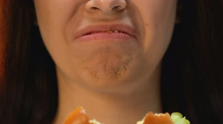 obnoxious : Woman eating hamburger with disgust, refusing unhealthy junk food, close up Stock Footage