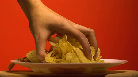 snoepen : Womans hand grabbing chips from plate, home party with junk food, slow motion
