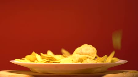 snoepen : Potato chips dropping on plate, junk food industry, tasty unhealthy snacks