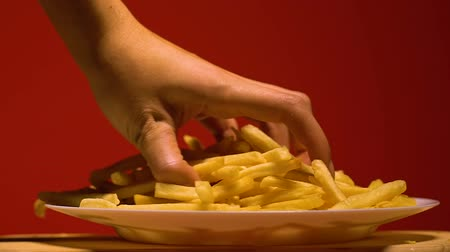 snoepen : Womans hand taking french fries from plate, junk food addiction, slow motion