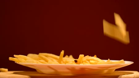 откорме : French fries dropping on plate, junk food industry, tasty but unhealthy snacks Стоковые видеозаписи