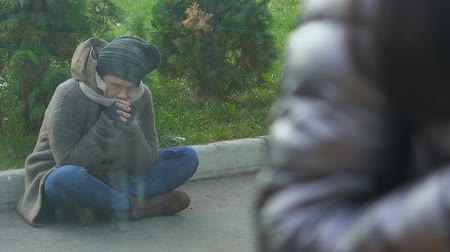 tramp : Poor homeless person sitting near cafe, watching people eating and laughing Stock Footage
