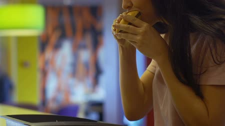 навынос : Hungry woman eating burger with great appetite, junk food addiction, overeating