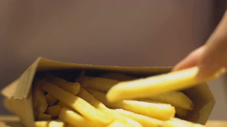 engorda : Woman enjoying taste of flavored french fries from fast food restaurant, obesity