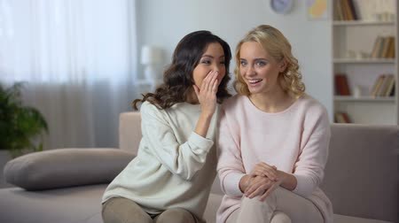 whispering : Woman telling story to female friend, having fun together at home, gossip