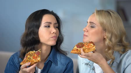 greedily : Hungry female friends enjoying delicious pizza, italian cuisine, food delivery