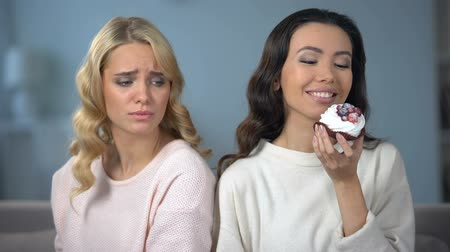 neid : Hungry woman on diet looking at her skinny friend enjoying tasty cake, envy