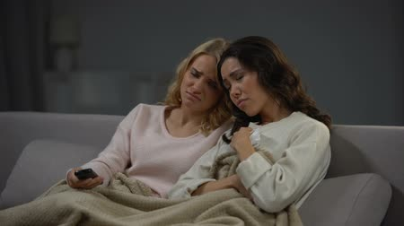 novela : Emotional women watching soap opera, sympathizing main heroes, relaxing at home