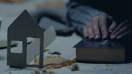 угождать : Refugee with Bible praying for home, dreaming of shelter, paper house as symbol