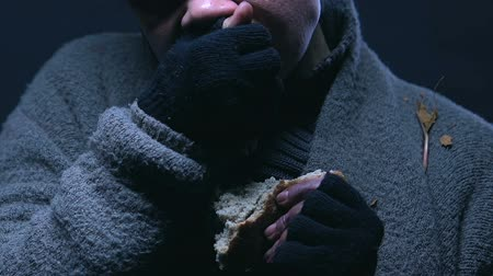 greedily : Beggar greedily eating bread, poverty and starvation problem, worldwide hunger Stock Footage