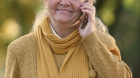 příznivý : Senior woman talking on cell phone, favorable tariffs for elderly, roaming
