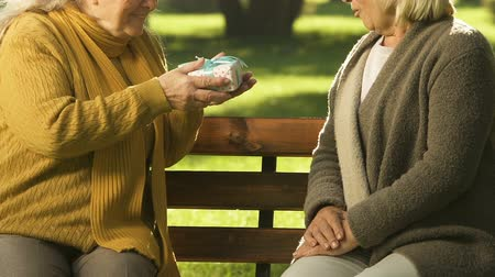 happy holidays : Senior woman giving present to friend, wishing happy birthday, pleasant surprise Stock Footage