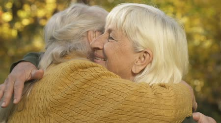 hugs : Old female friends hugging outside, sisters meeting, family connection, love