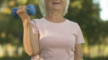 семидесятые годы : Smiling senior lady doing arm exercises with weight, lifting dumbbells, strength