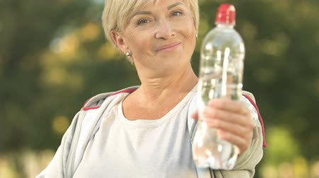 hidrasyon : Smiling sportswoman showing bottle of water and thumbs up, health care, activity Stok Video