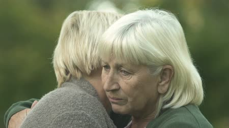 pensão : Depressed senior women hugging each other, friendship support, family problem