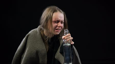 bídný : Female beggar with bruises on face drinking vodka with disgust alcohol addiction
