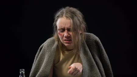 forced : Desperate woman with wounded face drinking vodka, trying to forget herself, pain