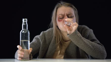 mistreatment : Hopeless alcohol addicted woman with wound on cheek pouring vodka in glass Stock Footage