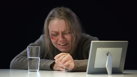 miserável : Depressed crying lady looking at photo taking antidepressant, violence victim