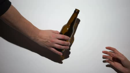 geri çekilme : Hand giving beer bottle to alcohol addict with self-inflicted arm, harmful habit Stok Video