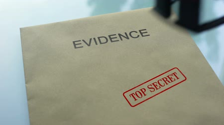 police sign : Evidence top secret, hand stamping seal on folder with important documents