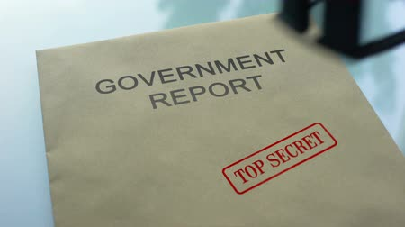 承認された : Government report top secret, stamping seal on folder with important documents