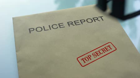 notarize : Police report top secret, hand stamping seal on folder with important documents Stock Footage