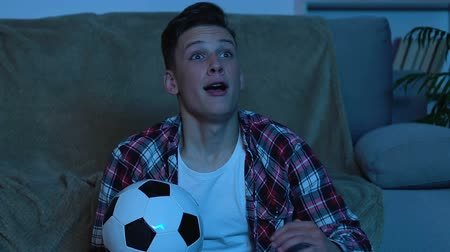 regozijo : Young man rejoicing favorite football team victory, watching match at home Stock Footage