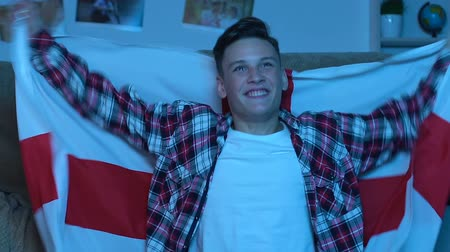 watch tv : Teenager with english flag watching match at home, supporting national team