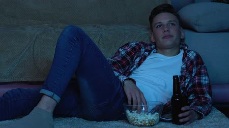 watch tv : Teenager lying on floor at home, watching TV, drinking beer and eating popcorn