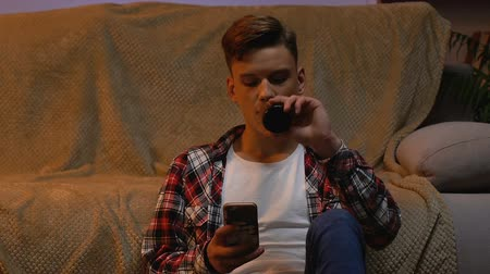 beer house : Boy drinking beer at home, chatting with friends in social network, awkward age